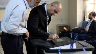 Iraqi election officials check an electronic vote-counting machine in Baghdad on 12 May 2018