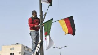 A worker in Algiers removes national and German flags in Algiers, Algeria - Monday 20 February 2017