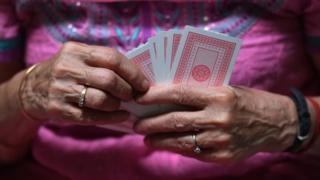 Bridge player Rita Choksi, 79, holds cards during an interview with AFP at her residence in New Delhi