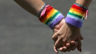 Dos mujeres con cintas arco iris se toman de las manos