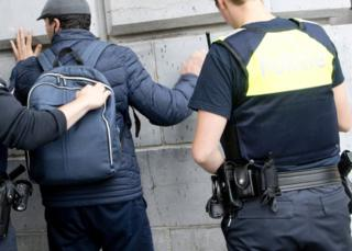 Police search a man's backpack at a station in Antwerp, 18 June
