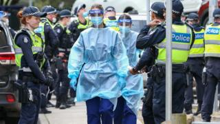 Medical staff wearing protective equipment walk through a police guard
