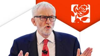Jeremy Corbyn in front of Labour logo