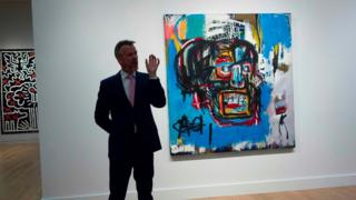 This file photo taken on May 5, 2017 shows a Sotheby's official speaking about Untitled, a 1982 painting by Jean-Michel Basquiat during a media preview at Sotheby's in New York.