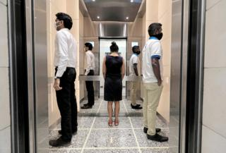 People stand in an elevator wearing face masks with their backs to each other