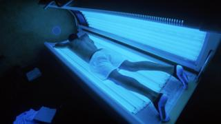 Man on a tanning bed