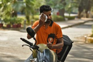A delivery boy wipes off his sweat on a hot day as temperature rises above 45 degree celsius, on June 2, 2019 in New Delhi, India.