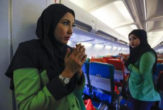 In this 22 December 2015, photo, Rayani Air flight crew pray before departure at Kuala Lumpur International Airport 2 in Sepang, Malaysia