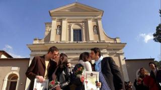 Parejas se besan frente a una iglesia de Terni