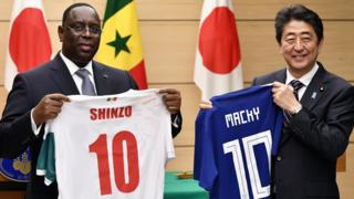 "Senegal""s President Macky Sall (L) and Japan""s Prime Minister Shinzo Abe (R) exchange national soccer jerseys at the end of a joint press conference at the Prime Minister""s official residence in Tokyo, Japan, 13 December 2017."