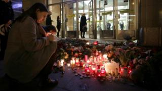 People light candles at memorial site for victims of blast in St. Petersburg metro