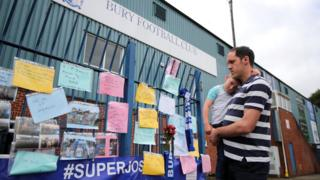 A fan reads messages at Gigg Lane