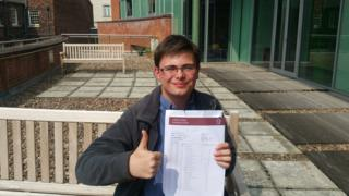 Daniel Lawson holding his exam certificates