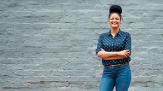 Mulher de camisa, calça-jeans, cabelos trançado preso no alto, sorrindo, com braços cruzados e em frente a uma parede
