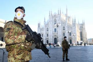 in_pictures Military officers wearing face masks stand outside Duomo cathedral, closed by authorities due to a coronavirus outbreak, in Milan. 24 February