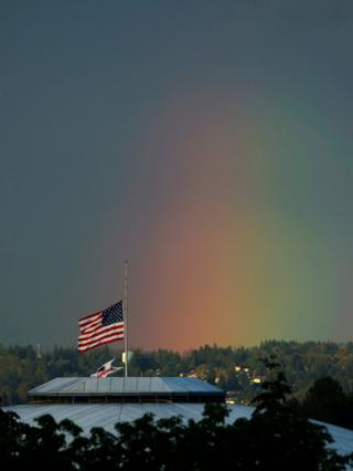 A rainbow appears behind the US flag flying at half-mast on top of the Tacoma Dome, Washington