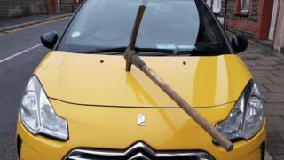 Damaged car with pickaxe in its bonnet