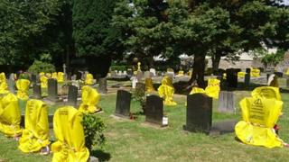 Headstones at the graveyard were covered in yellow plastic