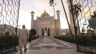 A Muslim man walks inside the Sultan Omar Ali Saifuddien mosque to perform the sunset prayer in Bandar Seri Begawan