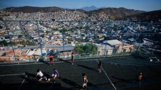 A wide shot of the favela beyond the chain-link fence of the training field