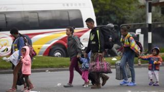 Migran-migran asal Venezuela berjalan dari terminal bus menuju kamp di Bogota