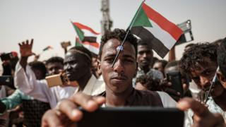 "A man poses for a ""selfie"" photo with a cell phone while having a miniature Sudanese flag placed on his forehead with a plastic suction cap as he awaits the arrival of the deputy head of Sudan's ruling Transitional Military Council (TMC) and commander of the Rapid Support Forces (RSF) paramilitaries, during a rally in the village of Abraq, about 60 kilometers northwest of Khartoum, on June 22, 2019."
