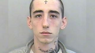 mug shot of tattooed man