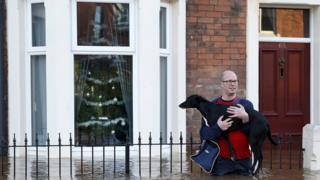 A man holds his dog as he wades through the flooded streets in Carlisle. Lots of people are having to carry their pets out of the their flooded homes to safety.