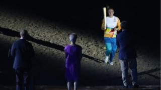 Sally Pearson carries the baton to the stage to be received by Prince Charles.
