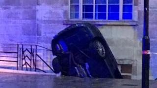 Car on its head on Lancaster Terrace, London