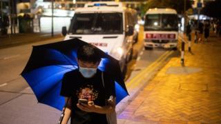 ativista perto de vans da polícia
