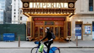A woman rides a bicycle past the closed Imperial Theatre in Times Square. 12 March 2020