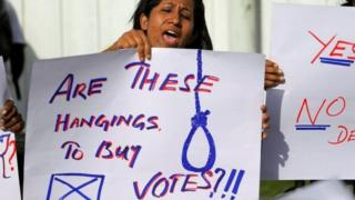 A woman protesting outside Welikada prison on 28 June holds a placard saying