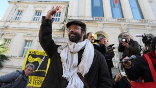French farmer Cedric Herrou waves as he arrives for his trial at the court of Nice, south-eastern France, on January 4, 2017 for allegedly assisting migrants to enter and remain illegally in France