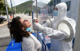A person in protective clothing swabs a woman's nose, with a transparent barrier diving them