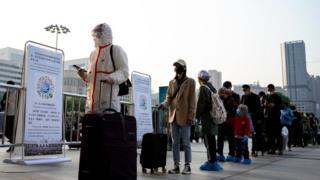Hankou Tren İstasyonu'nun önünde bekleyen bazı yolcular tüm vücutlarını koruyucu kıyafetler giyerken, bazıları sadece yüz maskesi taktı.