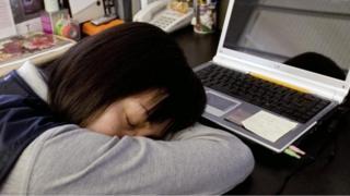 فتاة نائمة وهي تجلس على مكتب العمل