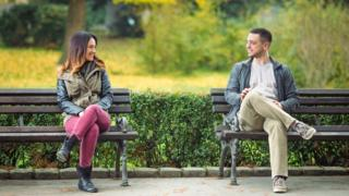 People talking to each other on a park bench