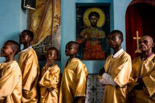 Boys and men dressed in golden robes stand next to ornate religious paintings inside the church