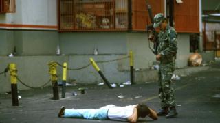 Militar armado frente a civil tumbado en el suelo en protestas desencadenadas en 1989.