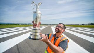Airfield operations manager Billy Hill with the famous Claret Jug on the runway