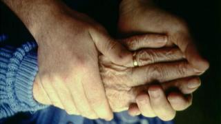 Elderly patient and carer holding hands