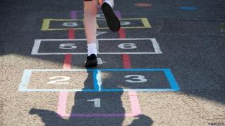 School girl playing hopscotch