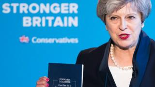 Theresa May holding the Conservative Party manifesto