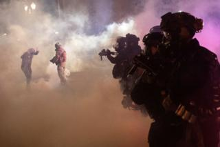 US federal law enforcement officers surrounded by tear gas
