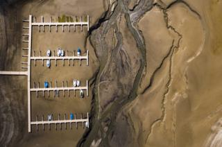 Stranded boats are pictured on the dried out shoes of the Lake of Gruyere.