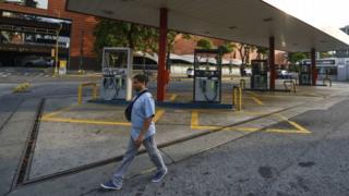 Un hombre caminando por una gasolinera abandonada.
