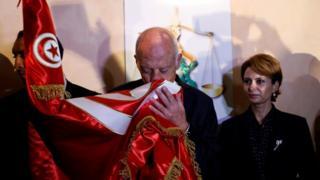 قيس سعيد يقبل العلم التونسي وزوجته إلى جواره