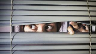 Woman looking through a blind