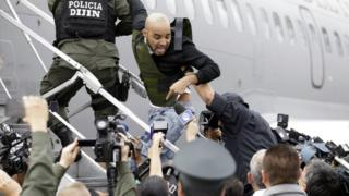 Alleged Peruvian drug trafficker Gerson Galvez shouts at the press as he is escorted by police officers into a Peruvian Air Force plane